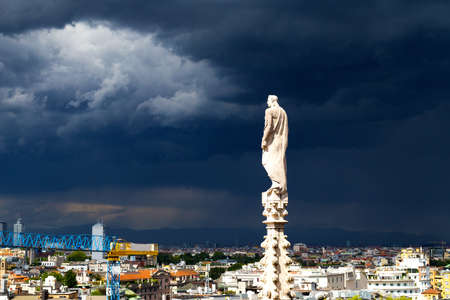 arial view: A statue of the Dome of Milan cathedral with the city view before the thunder  Arial view of Milan downtown from height of dome steeple
