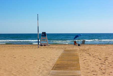 pause repas: Vacances � la plage. Chaises, parasol et �quipement de garanties laiss�s sans surveillance pendant la pause d�jeuner. Banque d'images