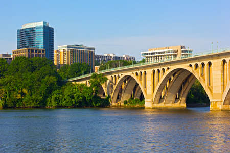 Key Bridge in Washington DC with office building on background. The bridge photographed from Georgetown Park in early summer morning.