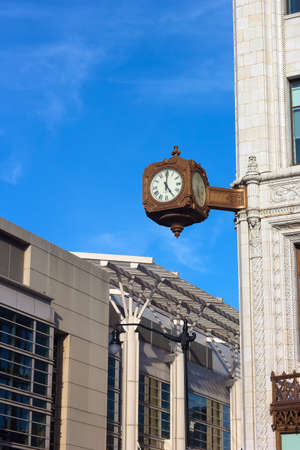 corner clock: Clock on the corner of historic building in Washington DC. A street clock against blue sky with thin clouds. Stock Photo