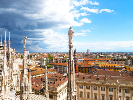 View on downtown from height of the Dome of Milan cathedral. Contrasting skies over roof tops of Milan downtown. photo