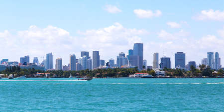 cruising: View on Miami city skyline from Miami Beach waterfront. Sailboats cruising of ocean waters at Miami Beach, Florida Stock Photo