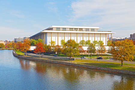Kennedy Performing Arts Center in autumn, Washington DC. Modern building of Kennedy Center and colorful trees are reflected in Potomac River.