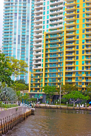 Miami suburb with residential buildings and palms near the canal. Suburban houses near water, pier and palm trees.