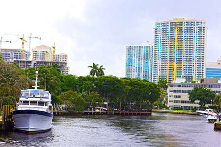 Miami suburb with residential buildings, palms and marine transport. Suburban houses near the canal with palms and boat.