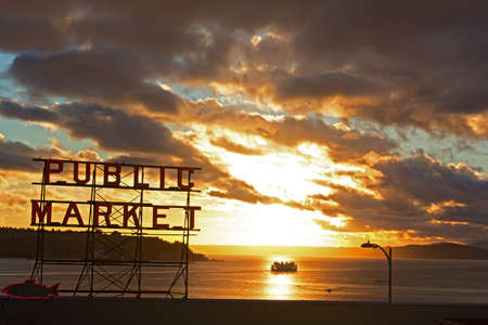 public market sign: Scenic sunset near Seattle public market. Sunset over the water with a neon public market sign and cruise ship.