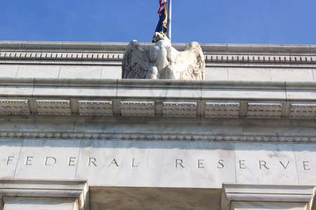 Federal Reserve building in Washington DC, US. Close up of a top part of the building with eagle statue. Imagens