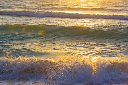 Ocean waves at sunrise in Miami Beach Florida. Sun shines on ocean waves in the morning. Фото со стока