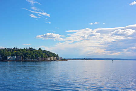 puget sound: Calm waters of Puget Sound before sunset in Seattle USA. Scenic panorama of Puget Sound in Seattle with mountains range on a horizon.