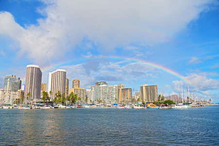 Rainbow over Waikiki beach resort and marina in Honolulu Hawaii USA. Scenic view of the Waikiki resort and marina with the Diamond Head Mountain on background. Фото со стока