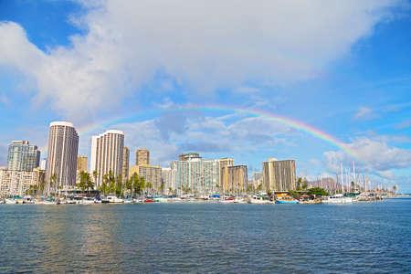 colorful sky: Rainbow over Waikiki beach resort and marina in Honolulu Hawaii USA. Scenic view of the Waikiki resort and marina with the Diamond Head Mountain on background. Stock Photo