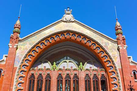 Facade of the Columbus Market, Valencia Spain. Modernist architecture of the market colorful facade under the sun.