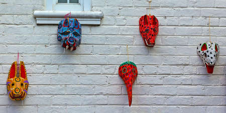 animal masks: Painted brick wall with wooden masks from Guatemala. Building exterior wall with colorful animal masks.