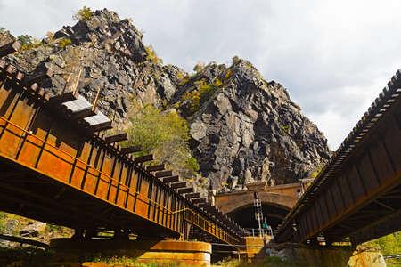 appalachian: Harpers Ferry train tunnel and bridge across Shenandoah River in West Virginia, USA. Train tracks above Appalachian trail along Blue Ridge mountains.