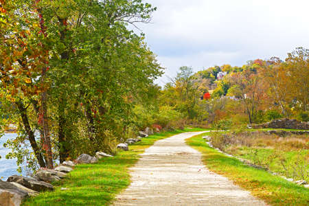 west river: Appalachian trail along Shenandoah River near Harpers Ferry historic town in West Virginia, USA. Autumn colors of deciduous trees and scenic view on Harpers Ferry town buildings.