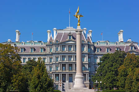 eisenhower: The First Division Monument and The Eisenhower Executive Office Building in Washington DC. The monument on a plaza in Presidents Park with Old Executive Office Building on background.