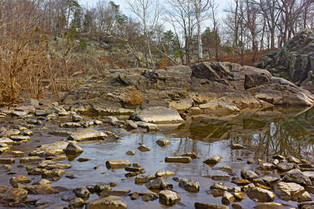 strenuous: Large rocks in the water at Great Falls Park, Maryland, USA. Forest and rocks near the water in winter.