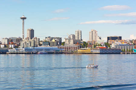 puget sound: Urban Seattle skyline along the city piers in Washington, USA. City sunset with reflections in the water of Puget Sound.