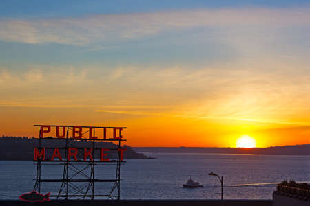 public market sign: SEATTLE, USA  FEBRUARY 15, 2015: Spectacular sunset over Puget Sound photographed from the Pike Public Market in Seattle on February 15, 2015. Winter sunset, water, mountains on horizon and Public Market neon sign. Editorial