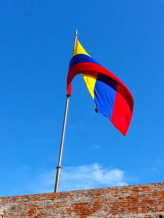 independencia: Colombian flag atop of San Filipe de Barajas Castle in Cartagena, Colombia. Tricolor country flag under a blue sky.