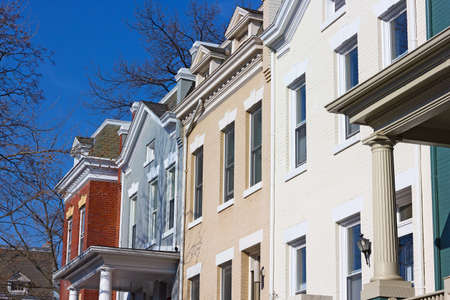 row of houses: Residential row houses in US Capital on a spring morning. Colorful brick townhouses of Washington DC. Stock Photo