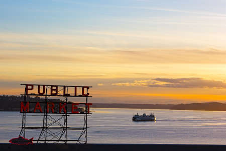 public market: SEATTLE, USA � MARCH 25, 2016: Sunset over Puget Sound in Seattle on March 25, 2016. Pike Public Market neon sign at sunset. Editorial