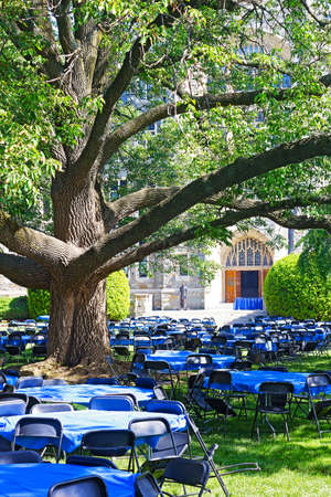 Lawn in front of White-Gravenor Hall with tables and chairs during Georgetown University reunion. Tables and chairs on a lawn under old tree.