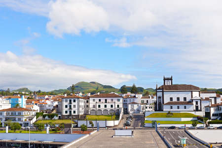View on Ponta Delgada from the ocean pier, Azores, Portugal. White houses with colorful tiled roofs and countryside with mountain ridge on the horizon.