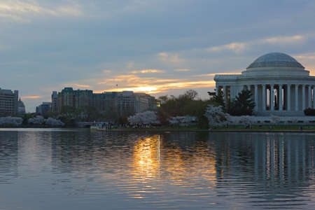 Thomas Jefferson Memorial at sunrise during cherry blossom festival in Washington DC, USA. Reflection of the memorial in waters of Tidal Basin. Stock Photo