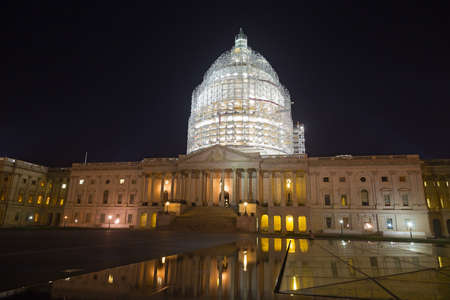 United States Capitol building in Washington, DC at night. The brightly lit dome is covered with scaffolding during comprehensive restoration in 2014-2016.