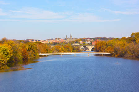 Autumn colors in Georgetown, Washington DC. A view on Georgetown University from Roosevelt Bridge over Potomac River. Stock Photo