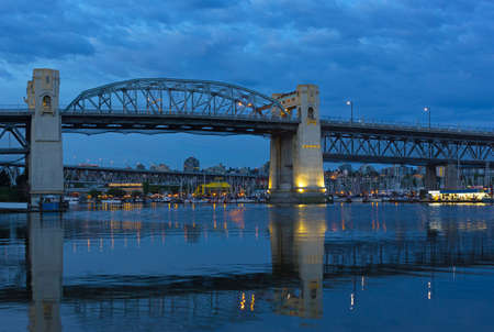 VANCOUVER, CANADA – JUNE 26: Burrard Bridge at dawn Granville Public Market with in a view on June 26, 2017 in Vancouver, Canada. Steel truss bridge over False Creek with imposing concrete towers before sunrise.