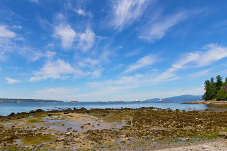 Sea coast during low tide near Stanley Park in Vancouver, Canada. Landscape with exposed sea rocks, ships and mountains on horizon.