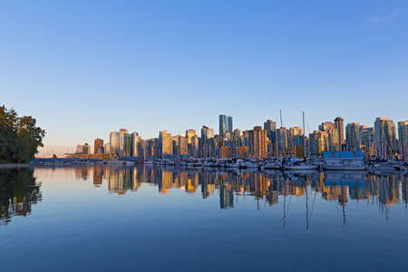 Vancouver downtown skyline reflection at sunset, Canada. Scenic urban landscape as seen from Stanley Park.