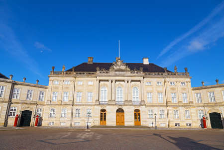 Amalienborg, the royal winter residence in Copenhagen, Denmark. Palace facade in early morning under a blue sky.
