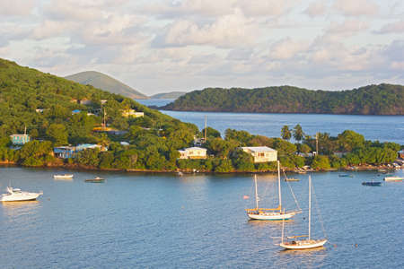 Tropical landscape of St Thomas Island near Coki Beach at sunrise, US VI. Yachts and boats moored in the Caribbean Sea bay.