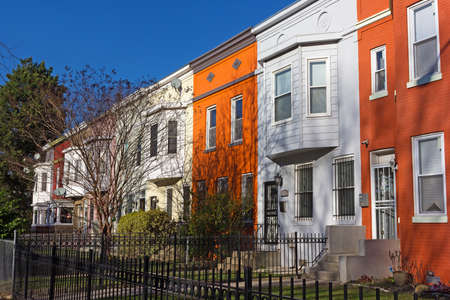 townhouses: Colorful townhouses under spring sun before sunset, Washington DC, USA. Historic townhouses in Shaw neighborhood on a quiet street. Stock Photo
