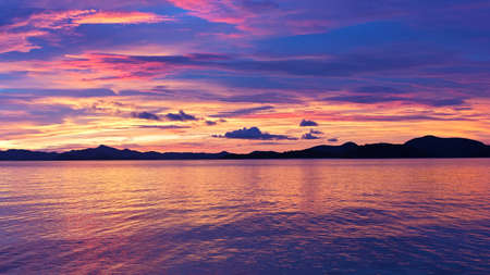 Majestic tropical sunset, Coron Island, Philippines. Sunset over the water with mountain ridges on horizon.