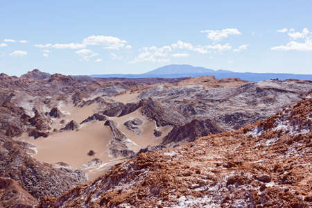 Colorful rock formations at high altitude in the desert with mountains on horizon. Natural wonders of Atacama Desert, Chile, South America.