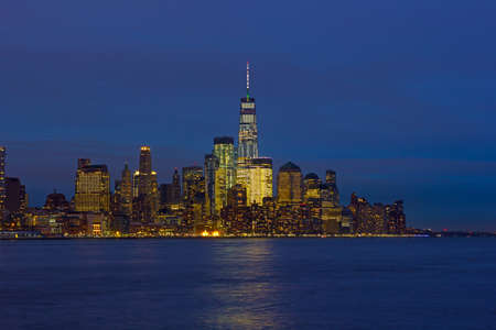 Low Manhattan skyline at night with reflection in Hudson River. New York urban panorama on a clear night in winter.