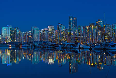 Vancouver city skyline at night in British Columbia, Canada. Modern building and waterfront marina with reflection in calm waters.