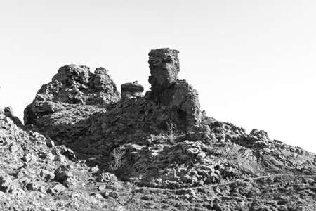 Stone giant guards a pathway through the mountain rocks in Iceland. Black and white photo of a rocky volcanic terrain. Stok Fotoğraf