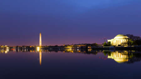 Washington DC panorama around Tidal Basin at sunrise during cherry blossom. City landmarks with reflection in dark waters at dawn.