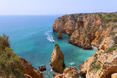 Sightseeing of sandstone cliffs and grottoes by boat is one of popular pastime activity in Lagos, Portugal. Algarve coastline on a sunny morning in spring. Stockfoto