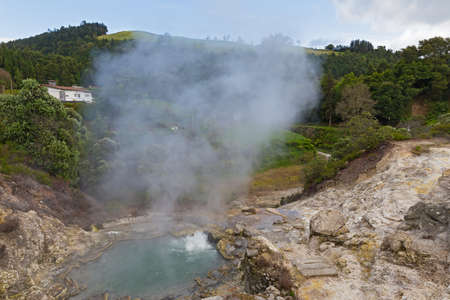 Hot spring surrounded by volcanic terrain and mountainous landscape in Furnas, Azores, Portugal. Summer landscape of Azorean village on a cloudy day.