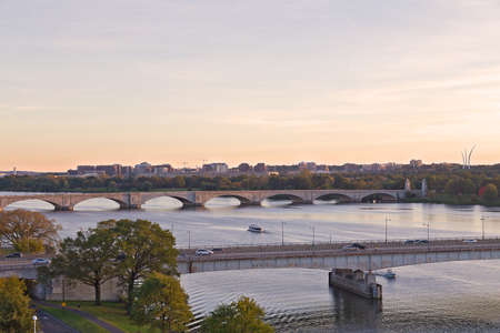 Washington DC panorama with bridges across Potomac River at sunset. Scenic view on US capital landscape in early fall.