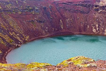 Distinctive red rock and vegetation on one edge of a volcanic crater lake in south Iceland. A beauty of easy recognizable volcanic crater lake in Iceland, Europe.