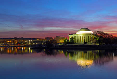 Tidal Basin panorama at dawn with Thomas Jefferson Memorial during cherry blossom festival in Washington DC, USA. In anticipation of sunrise colorful reflection of buildings in calm water of the Tidal Basin reservoir.