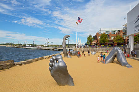 OXON HILL, MARYLAND, USA - SEPTEMBER 11, 2016: Awakening Sculpture at National Harbor. A famous statue of a giant embedded in the earth created by J. Seward Johnson Jr.