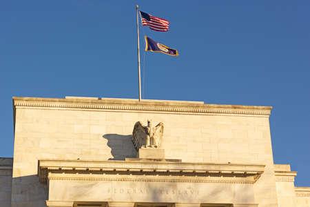 Sede della Federal Reserve degli Stati Uniti a Washington DC, USA. Eccles Building con bandiere nazionali e federali statunitensi sotto il cielo limpido al mattino presto.